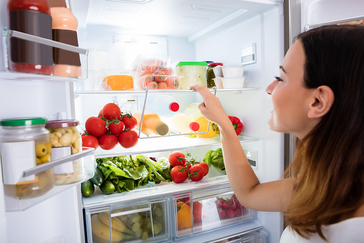 smiling woman looks at food in a clean refrigerator