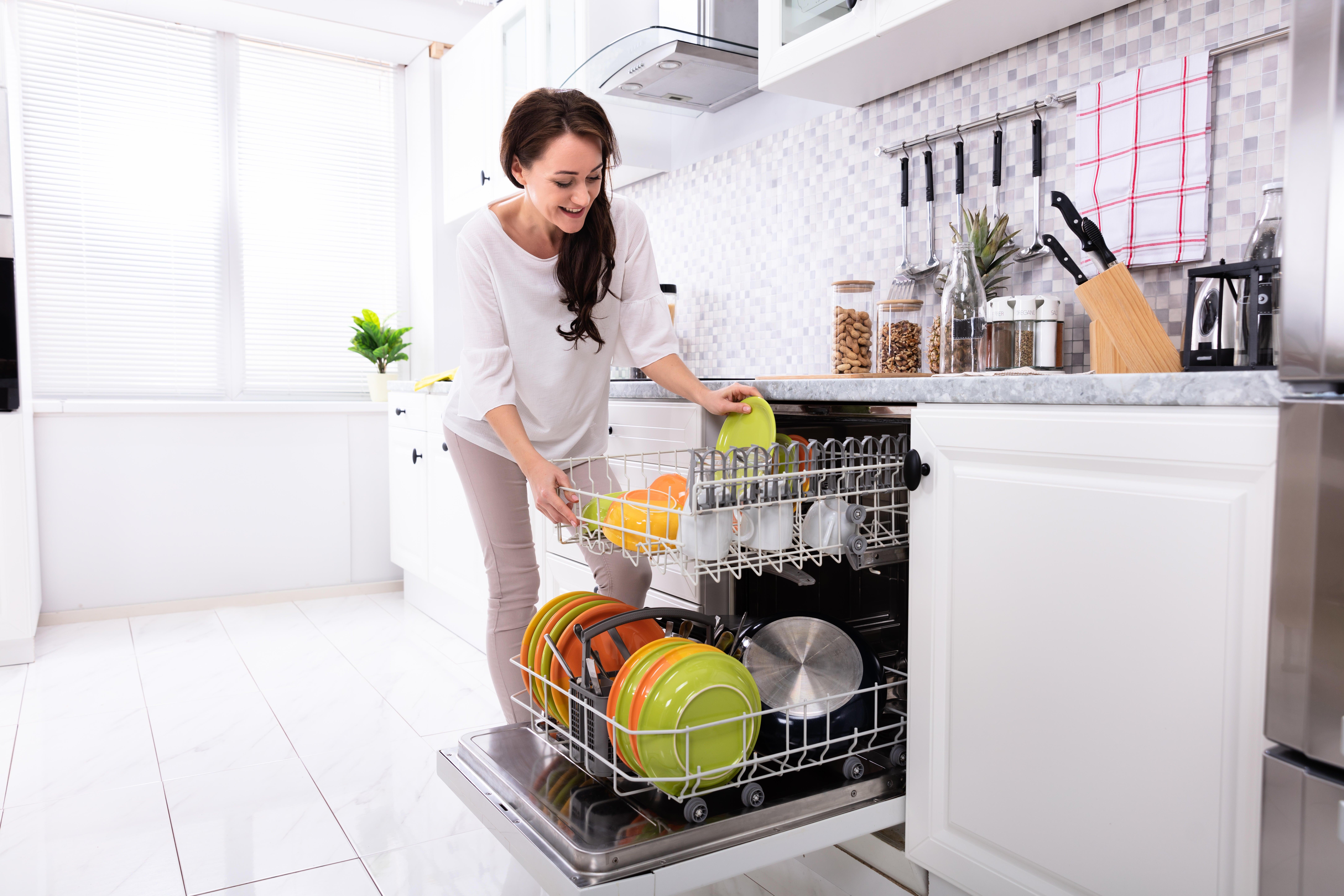 woman loads a dishwasher in a modern kitchen