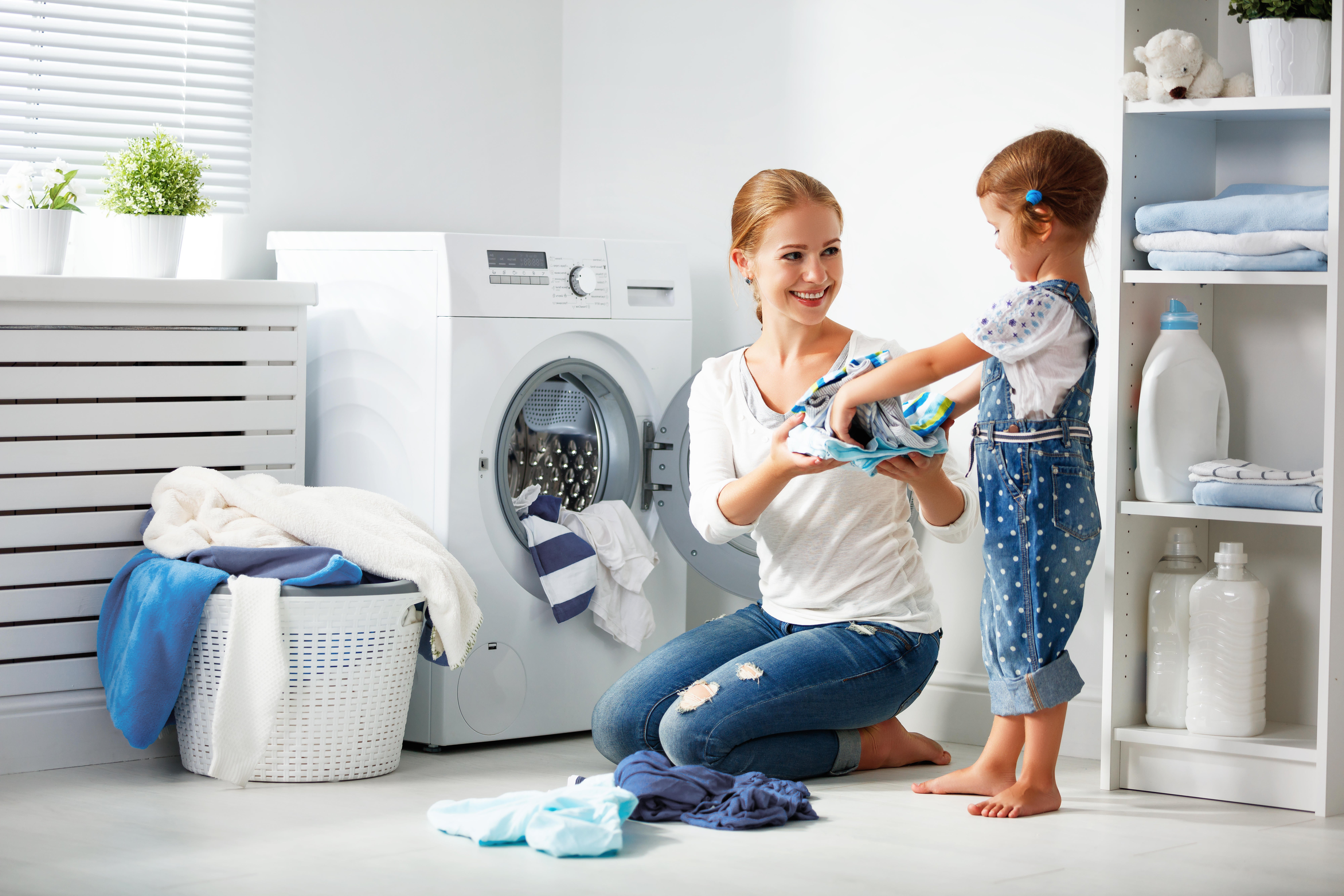 woman folds her daughter's laundry beside a modern clothes dryer
